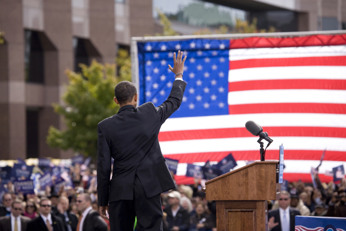 Presidential Candidate Barack Obama waves to crowd as he is framed against American Flag at early vote for change Presidential rally October 29, 2008 at Halifax Mall, Government Complex in Raleigh, NC