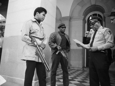 Two members of the Black Panther Party are met on the steps of the State Capitol in Sacramento, May 2, 1967, by Police Lt. Ernest Holloway, who informs them they will be allowed to keep their weapons as long as they cause no trouble and do not disturb the peace. Activist scott crow says the Black Panthers inspired his own theory of liberatory community armed self-defense.