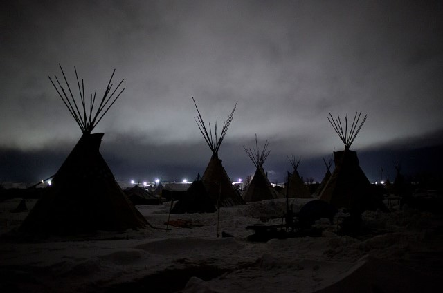 Giant flood lights set up by a pipeline company and law enforcement illuminate a cloudy winter night at the Oceti Sakowin camp just outside of the Lakota Sioux reservation of Standing Rock, North Dakota, on December 1, 2016.