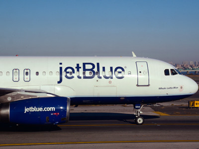 A JetBlue passenger jet (Embraer 190) taxis at LaGuardia Airport in New York, New York.