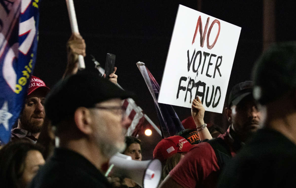 """A """"no voter fraud"""" sign is displayed by a protester at the Maricopa County Elections Department office on November 4, 2020, in Phoenix, Arizona."""