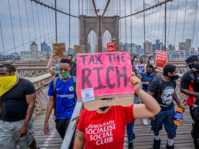 "A protester in a red DEMOCRATIC SOCIALIST CLUB t-shirt holds a sign reading ""TAX THE RICH"" at a protesy\t"
