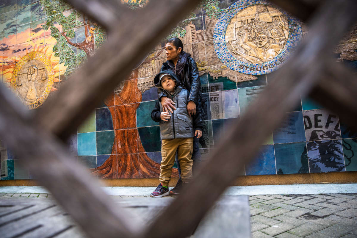 Juthaporn Chaloeicheep, 44, and son Douglas Jones, 5, stand for a portrait in the courtyard of Arnett Watson Apartments, a permanent supportive housing community where they reside in the Tenderloin district of San Francisco, California, on March 16, 2021.