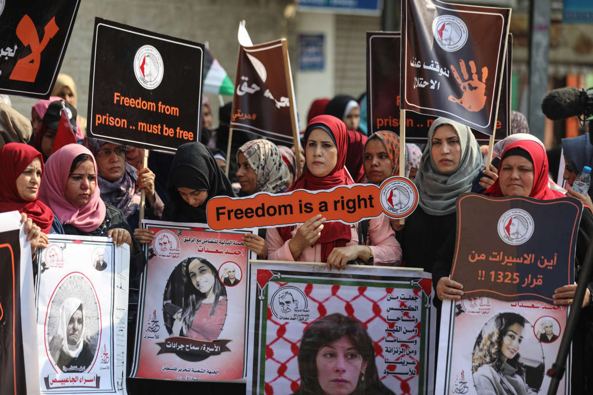 Palestinian women hold placards as they gather for a demonstration in support of Palestinian woman prisoners in Israeli jails in front of the International Committee of the Red Cross building in Gaza City, Gaza, on November 6, 2019.
