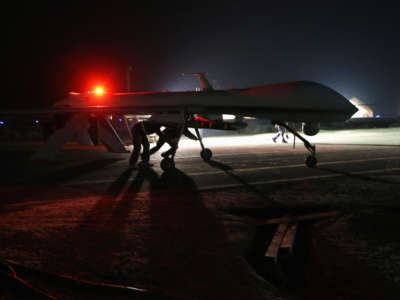 Contract workers push a U.S. Air Force MQ-1B Predator unmanned aerial vehicle after it flew a mission from an air base in the Persian Gulf region on January 7, 2016.