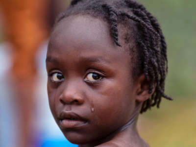A little girl cries while looking into the camera