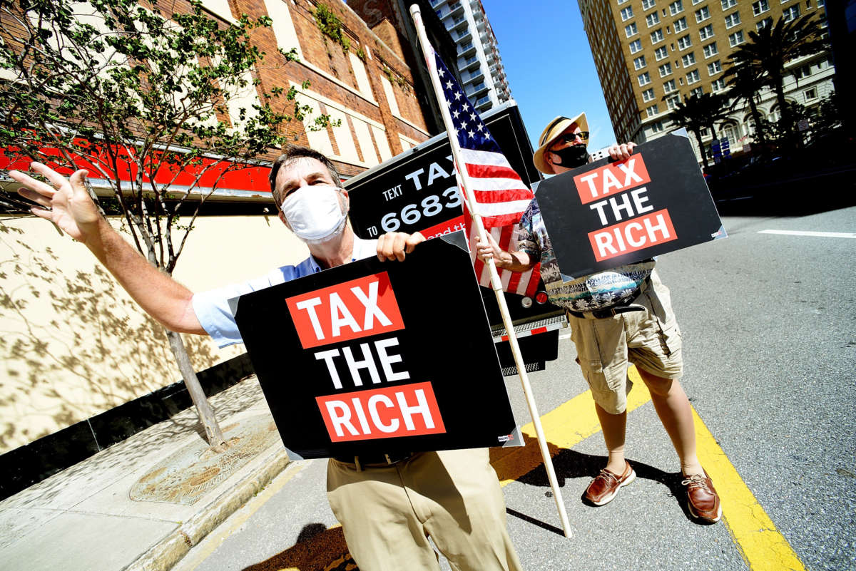 John Stewart, left, and Jay Alexander of MoveOn call on Senator Marco Rubio's office to increase federal taxes to big corporations on May 17, 2021, in Tampa, Florida.
