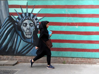 A woman passes a mural painted on the wall of the former US Embassy in Tehran, Iran, on May 9, 2018.