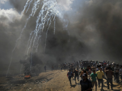 Protesters run away from tear gas dispersed by Israeli forces as they inch closer to the border fence separating Israel and Gaza on May 14, 2018, in a camp east of Gaza City, Gaza.