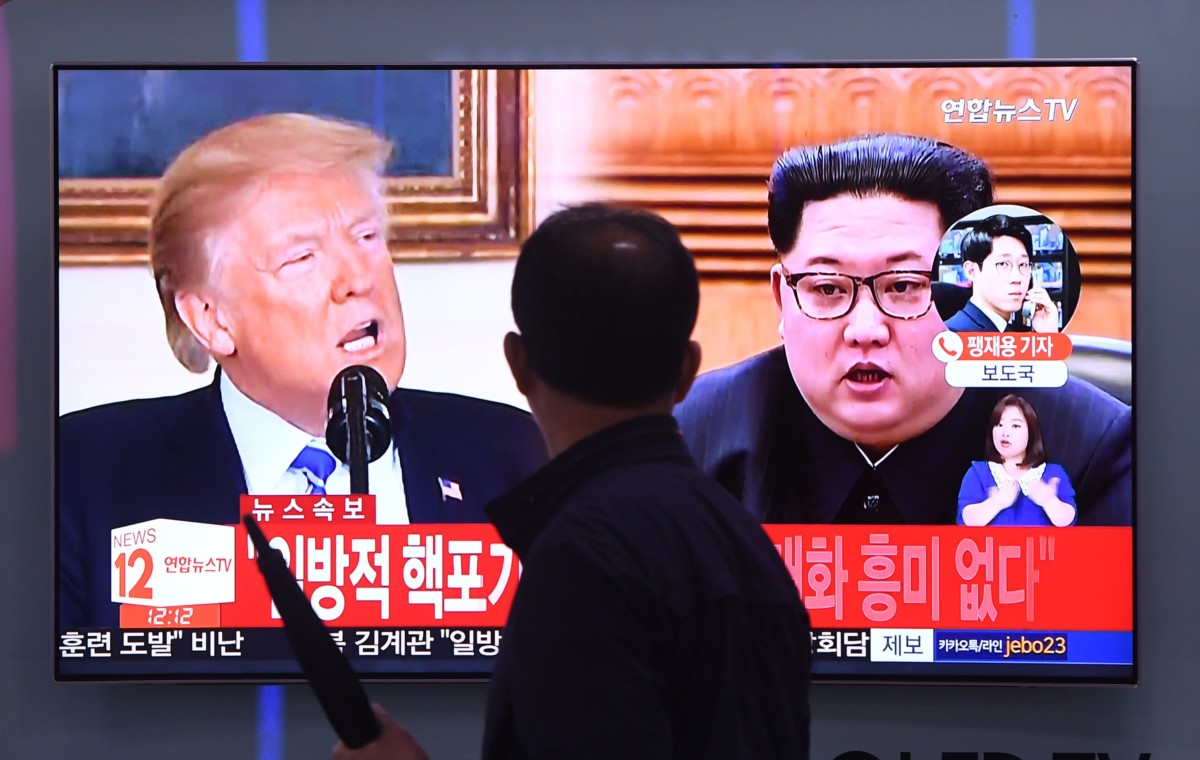 A man walks past a television news screen at a railway station in Seoul, South Korea, showing North Korean leader Kim Jong Un and Donald Trump on May 16, 2018.