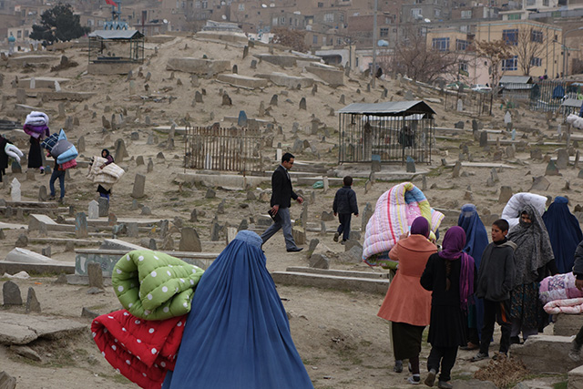Bearing quilted bed covers, Afghans walk through the cemetery to their mountainside homes. (Photo: Courtesy of Carolyn Coe)