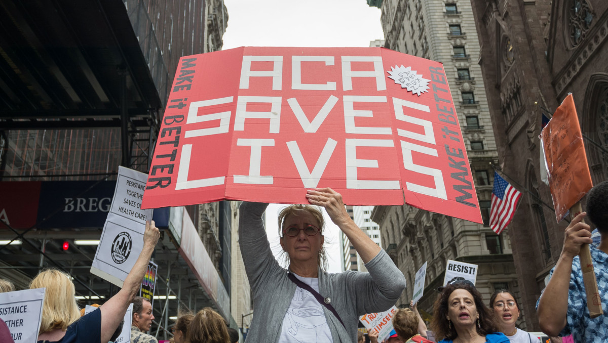 Participants hold signs while protesting the repeal and replacement of the Affordable Care Act during a rally on July 29, 2017.