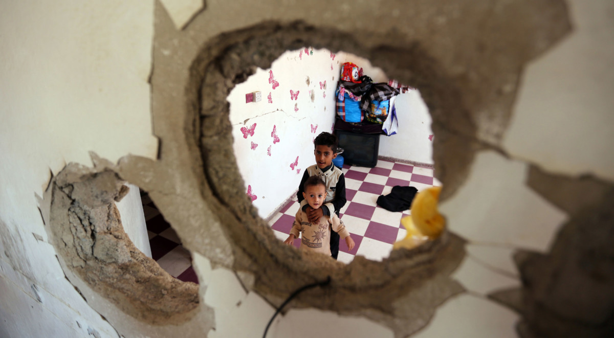 Displaced Yemeni children from the Hodeidah province are pictured on September 30, 2018, through a hole in a damaged house where they have been living with other displaced families in the southwestern Yemeni city of Taez. The conflict has triggered what the UN describes as the world's worst humanitarian crisis, with 22 million people in need of humanitarian aid.