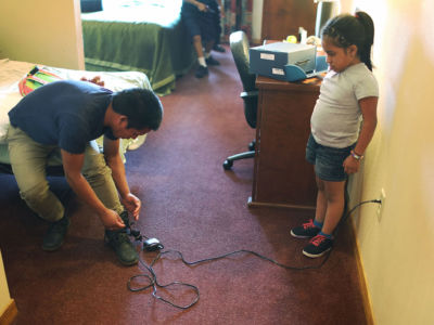 A young girl watches as her father plugs in his ankle monitor for charging at an Annunciation House facility after being reunited with each other on July 25, 2018, in El Paso, Texas. Originally from Guatemala, the two were separated for about two months after attempting to cross into the US.