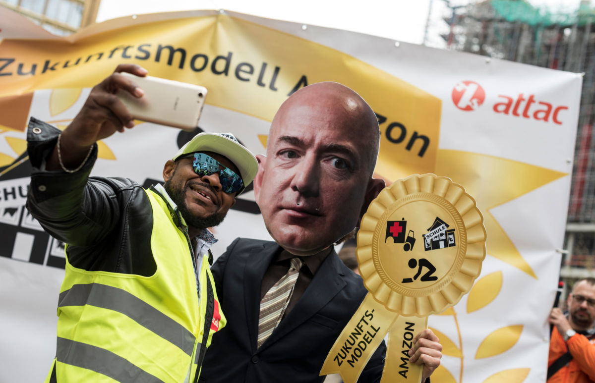 An Amazon warehouse worker shoots a selfie with an activist dressed as Amazon CEO Jeff Bezos during a protest in Berlin, April 2018.
