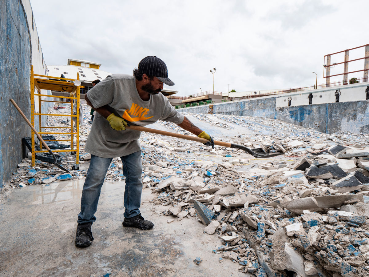 Workers shovel debris from the swimming and diving pool in the Aquatic Center at the Albergue Olympic Training Center of Puerto Rico on November 14, 2018, in Salinas, Puerto Rico.