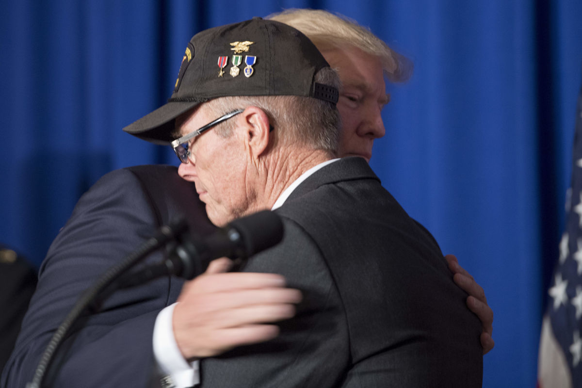 Donald Trump hugs Vietnam veteran Max Morgan as he participates in a veterans meet and greet on the sidelines of the Asia-Pacific Economic Cooperation leaders' summit in the central Vietnamese city of Danang on November 10, 2017.