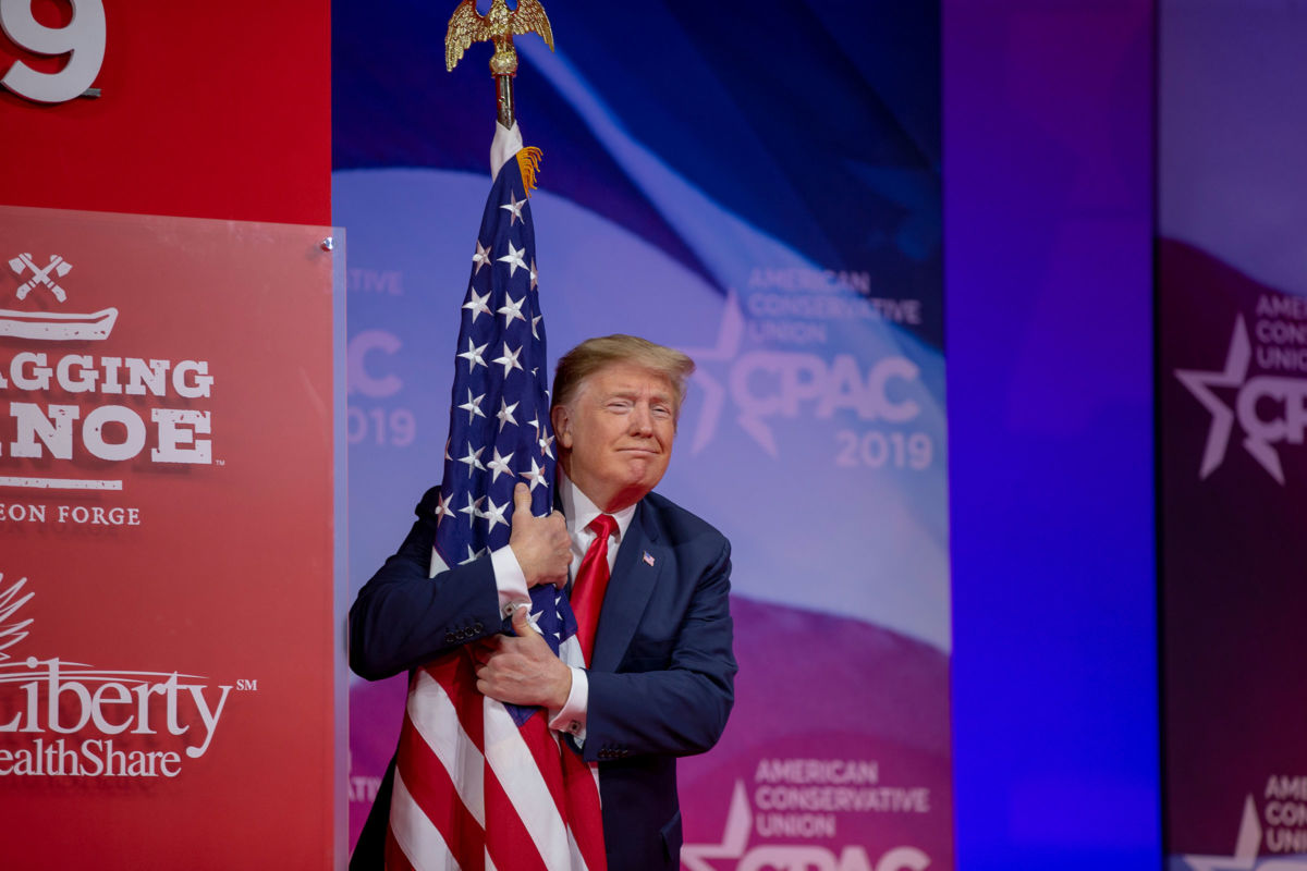 President Donald Trump hugs the U.S. flag during CPAC 2019 on March 2, 2019 in National Harbor, Maryland.