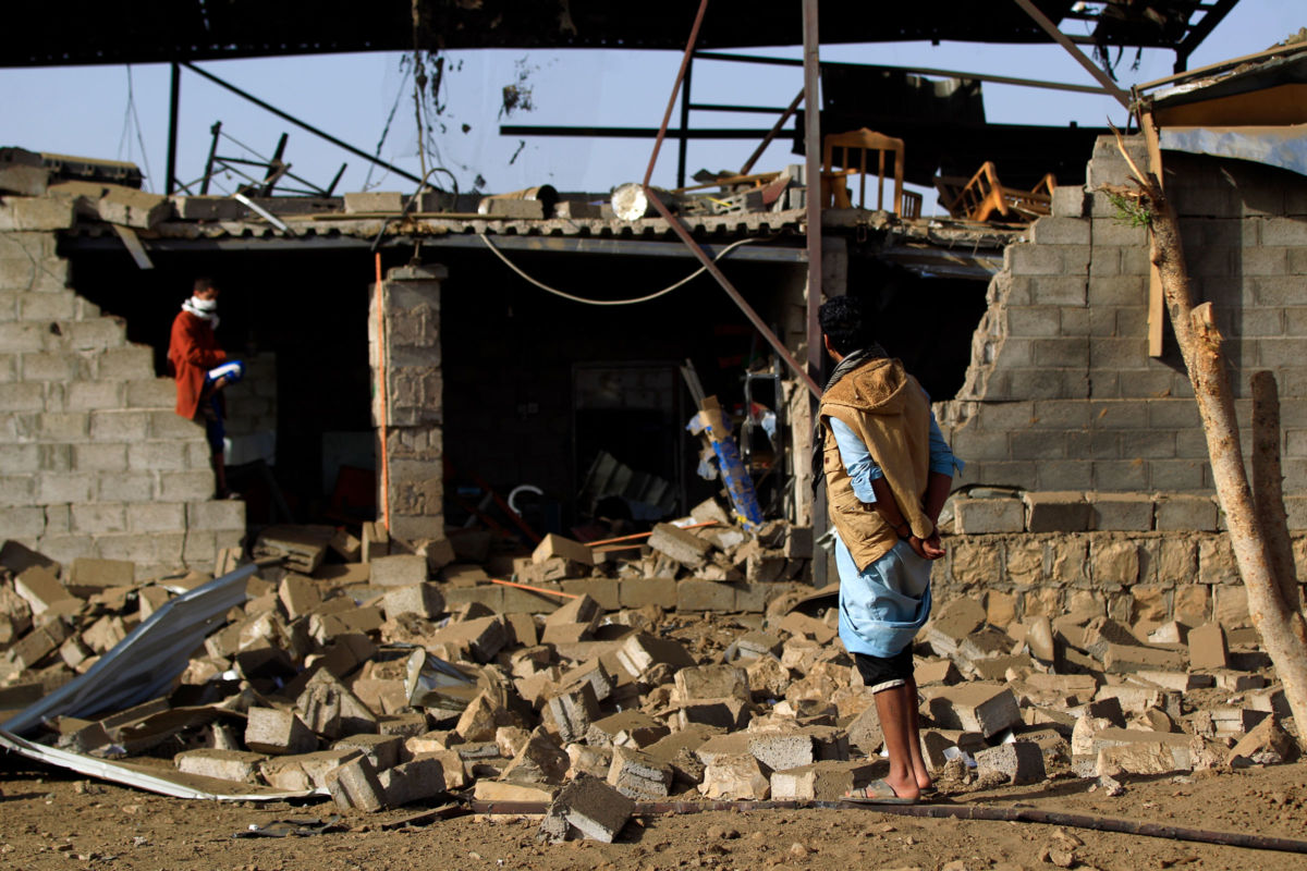 Man stands amid the rubble from airstrike in Yemen.