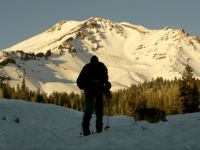 A hiker standing in the snow is silhouetted against a bright, snow-capped mountain