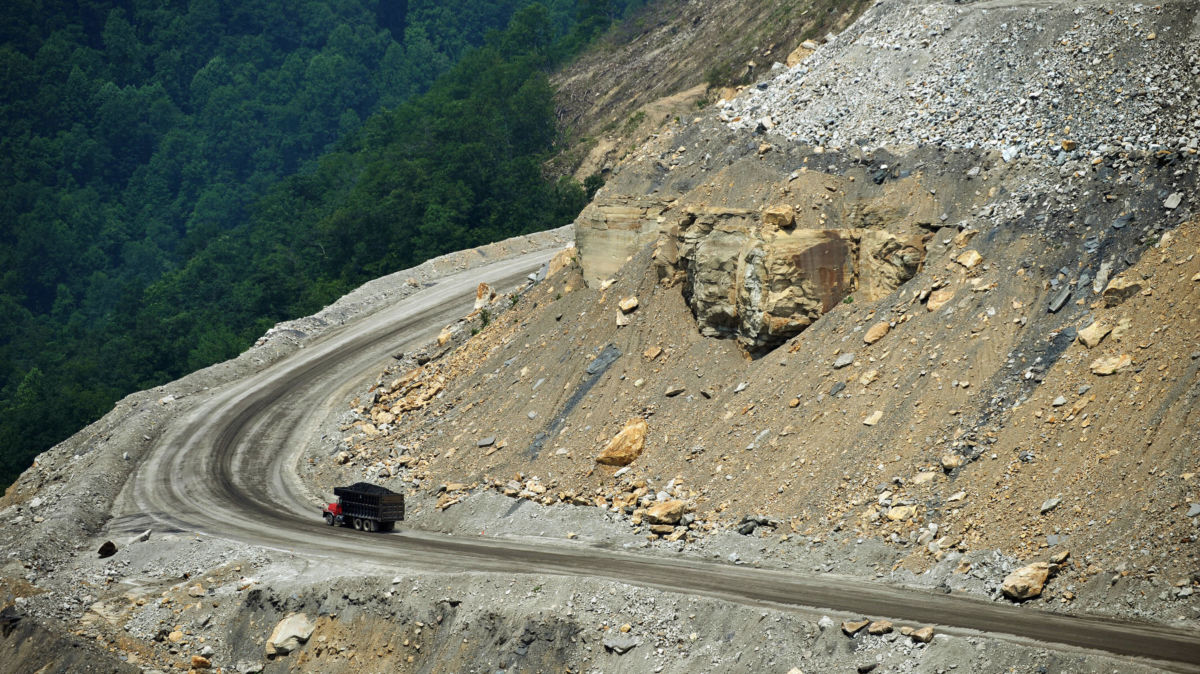 A dumptruck drives up a mined mountain as a forest is seen in the background