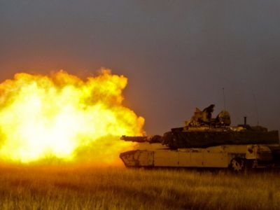 A tank shoots a missile in a fiery explosion