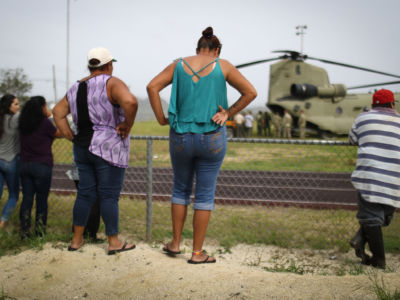 Local residents watch after a U.S. Army helicopter landed during food and water delivery efforts four weeks after Hurricane Maria struck on October 18, 2017, in Utuado, Puerto Rico.
