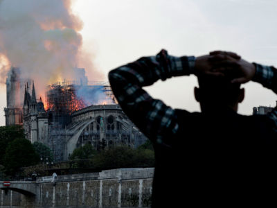 A man watches the landmark Notre Dame Cathedral burn in central Paris on April 15, 2019.