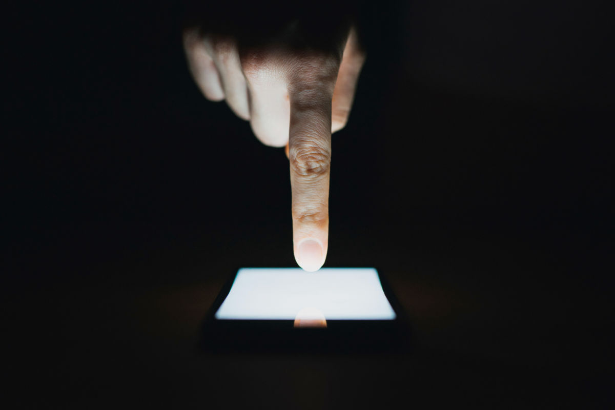 A closeup of a white hand touching a lit smartphone screen
