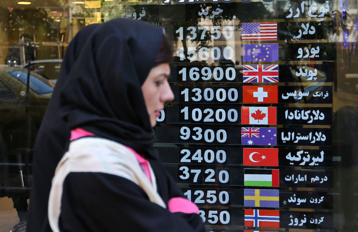 An Iranian woman walks past a currency exchange shop in the capital Tehran