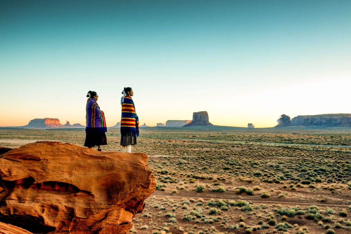 Two Navajo women stand on a cliff overlooking rock formations