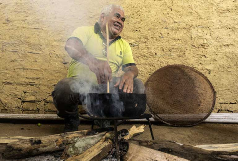 César de Mendes, a small-scale manufacturer who specializes in Amazon chocolates, helps the Yanomami toast cacao seeds in the chocolate making process.