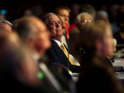 David Koch's face is seen amidst a crowd