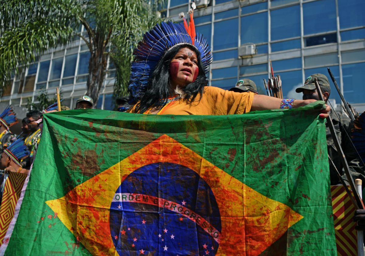 A woman in a headdress holds a Brazilian flag splattered with red paint to simulate bloodstains