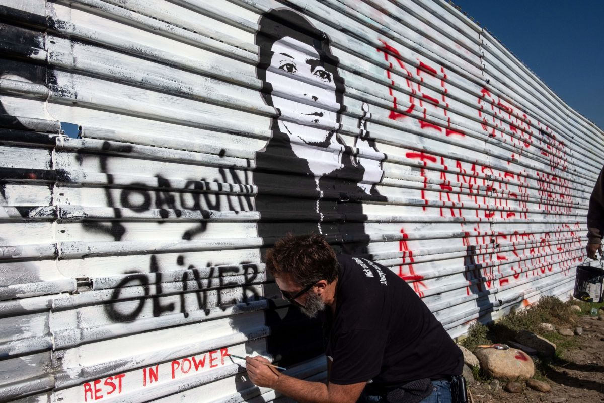 "Venezuelan artist Manuel Oliver, father of slain Joaquin Oliver, works on a mural on the U.S.-Mexico border fence reading ""On the other side they also kill our sons"" in Tijuana, Baja California State, Mexico, on December 19, 2018."