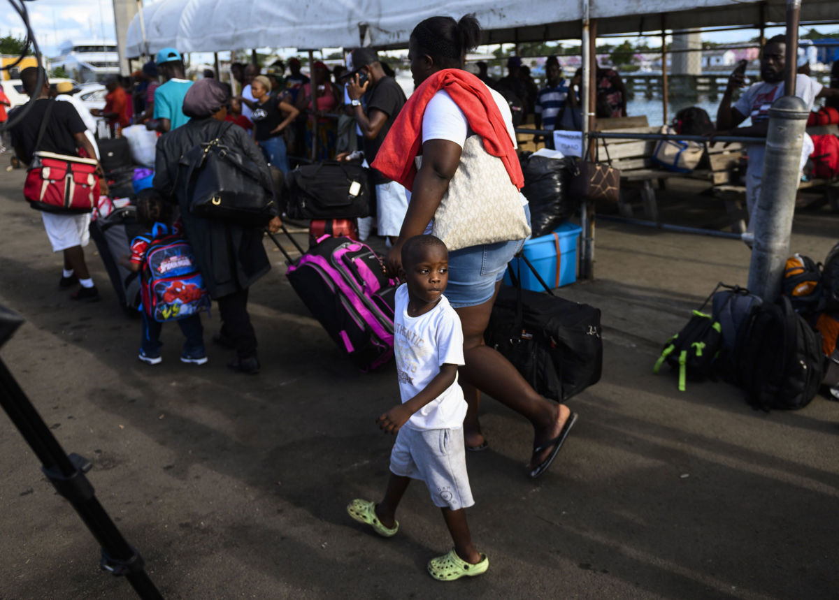 Evacuees in Nassau, Bahamas, wait on September 9, 2019, to board a bus heading to a shelter.