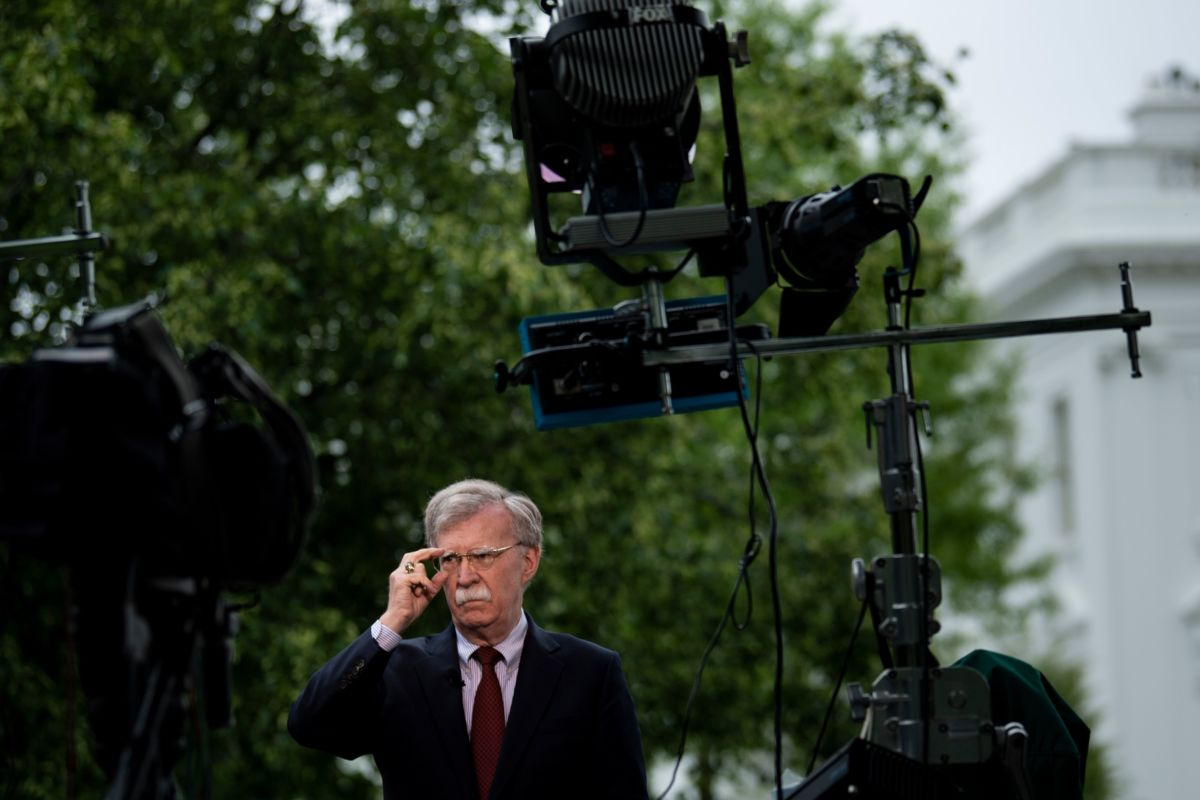 John Bolton adjusts his glasses in front of microphones while being questioned by the press