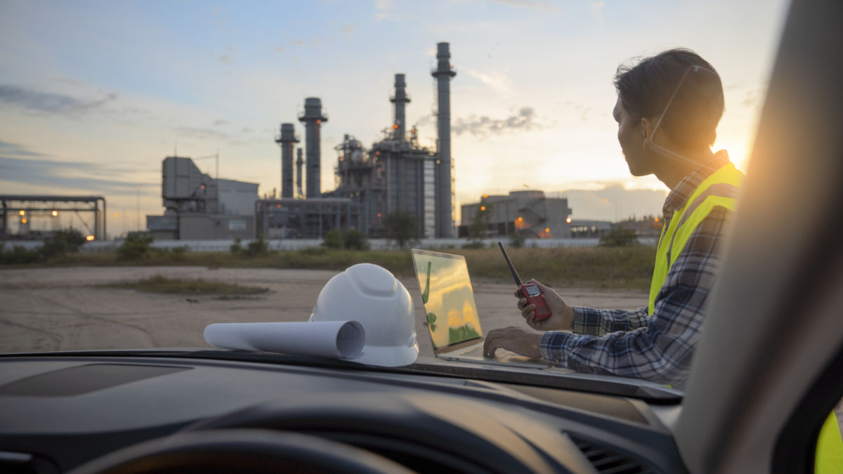 A worker looks onward at a chemical processing plant