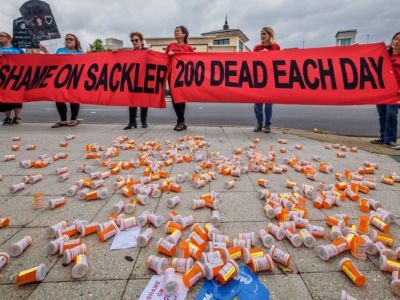 "Activists hold a red banner reading ""SHAME ON SACKLER; 200 DEAD EACH DAY"" while standing in front of empty pill bottles scattered on the sidewalk"