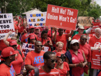 Workers wearing red shirts display signs during a protest