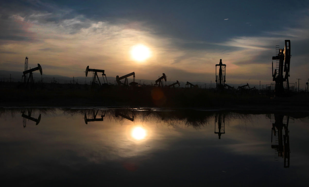 Oil pumps and equipment reflect on water in the South Belridge oil field in Kern County, the fourth largest oil field in California.