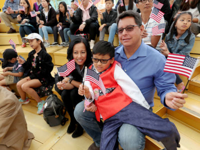 A father sits with his two children, all of whom are waving tiny US flags