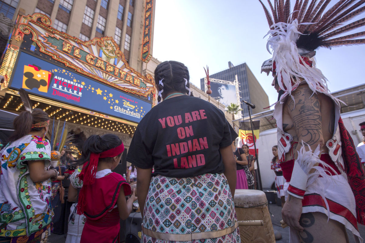 Dancers from Anahuacalmecac International University Preparatory of North America school for indigenous students pray before dancing on Hollywood Boulevard near the El Capitan Theatre during an event celebrating Indigenous Peoples' Day on October 8, 2017, in Los Angeles, California.