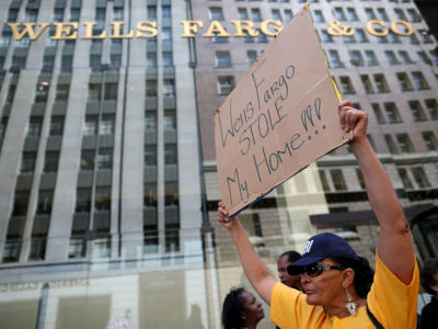 "A woman holds a sign reading ""WELLS FARGO STOLE MY HOME"" during a protest"