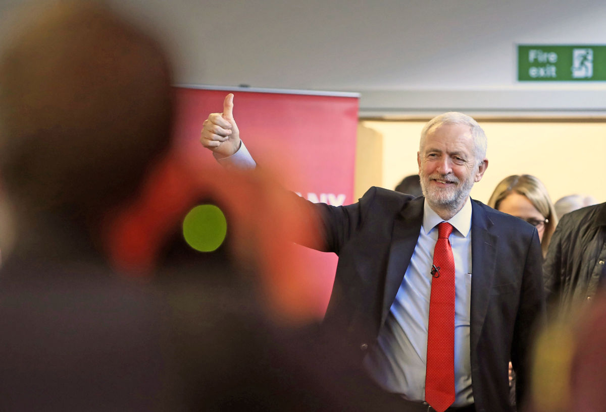 Jeremy Corbyn walks into a room and gives a thumbs up to the crowd
