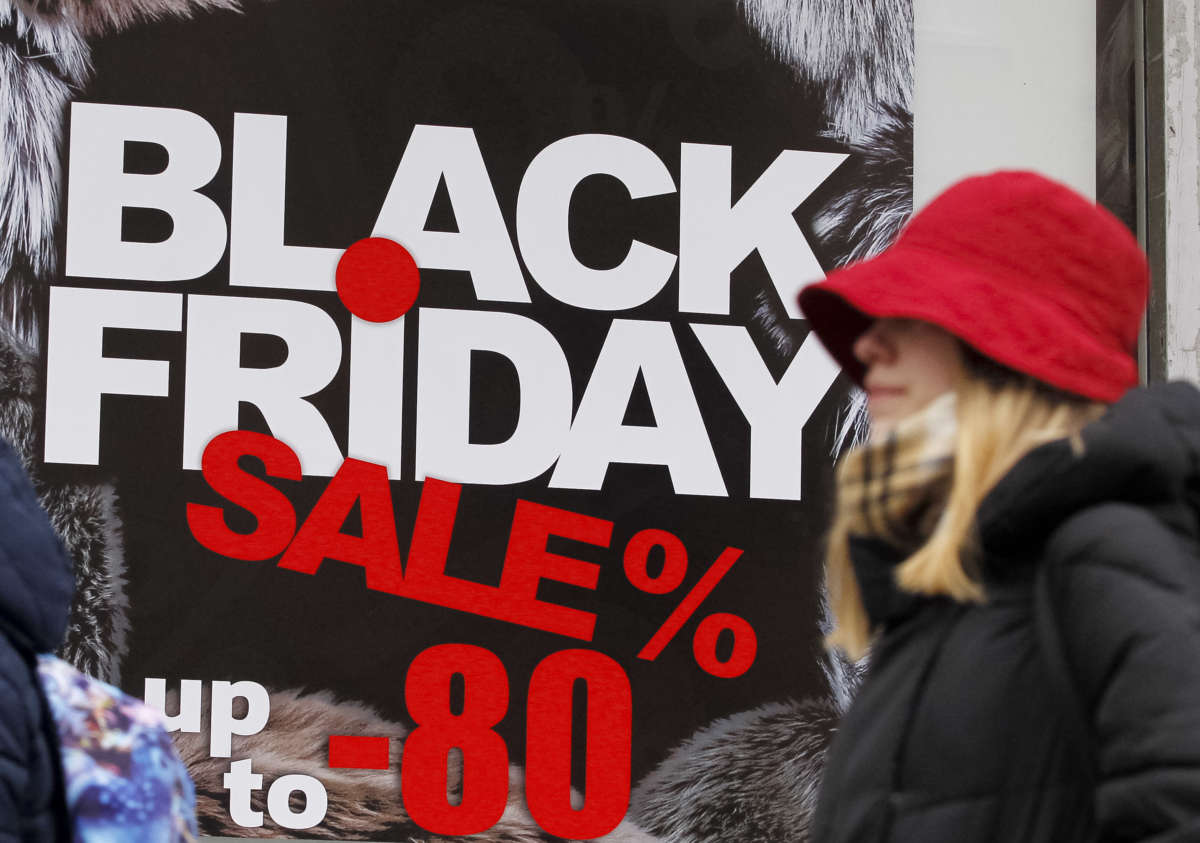 A woman in a red hat walks by an advertisement for a black friday sale
