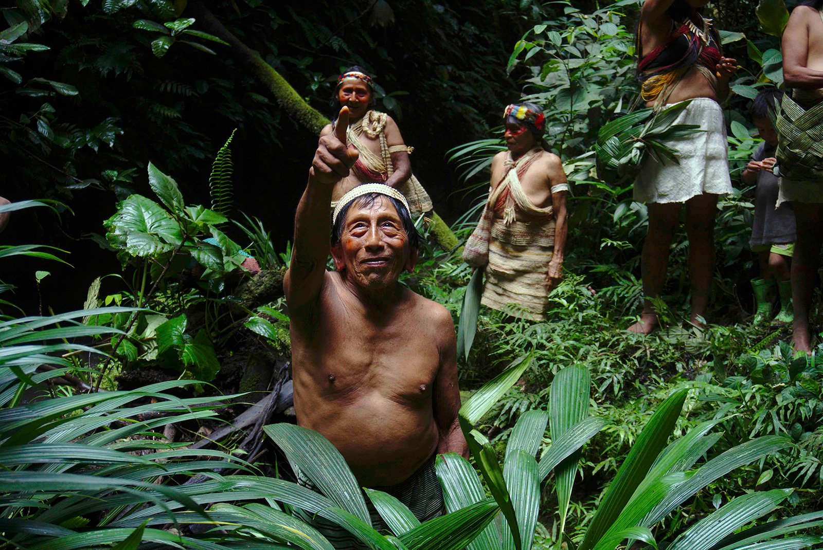 A Waorani elder looks above at the forest canopy near a sacred waterfall at the community of Nemonpare, Waorani territory, Ecuadorian Amazon.