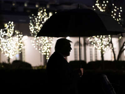 President Trump is seen in silhouette holding an umbrella as he talks to members of the press on the South Lawn of the White House, December 10, 2019.