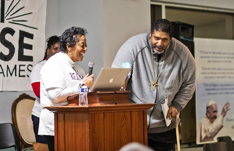 Sharon Lavigne speaks into a microphone at a podium as Rev. William Barber stands nearby