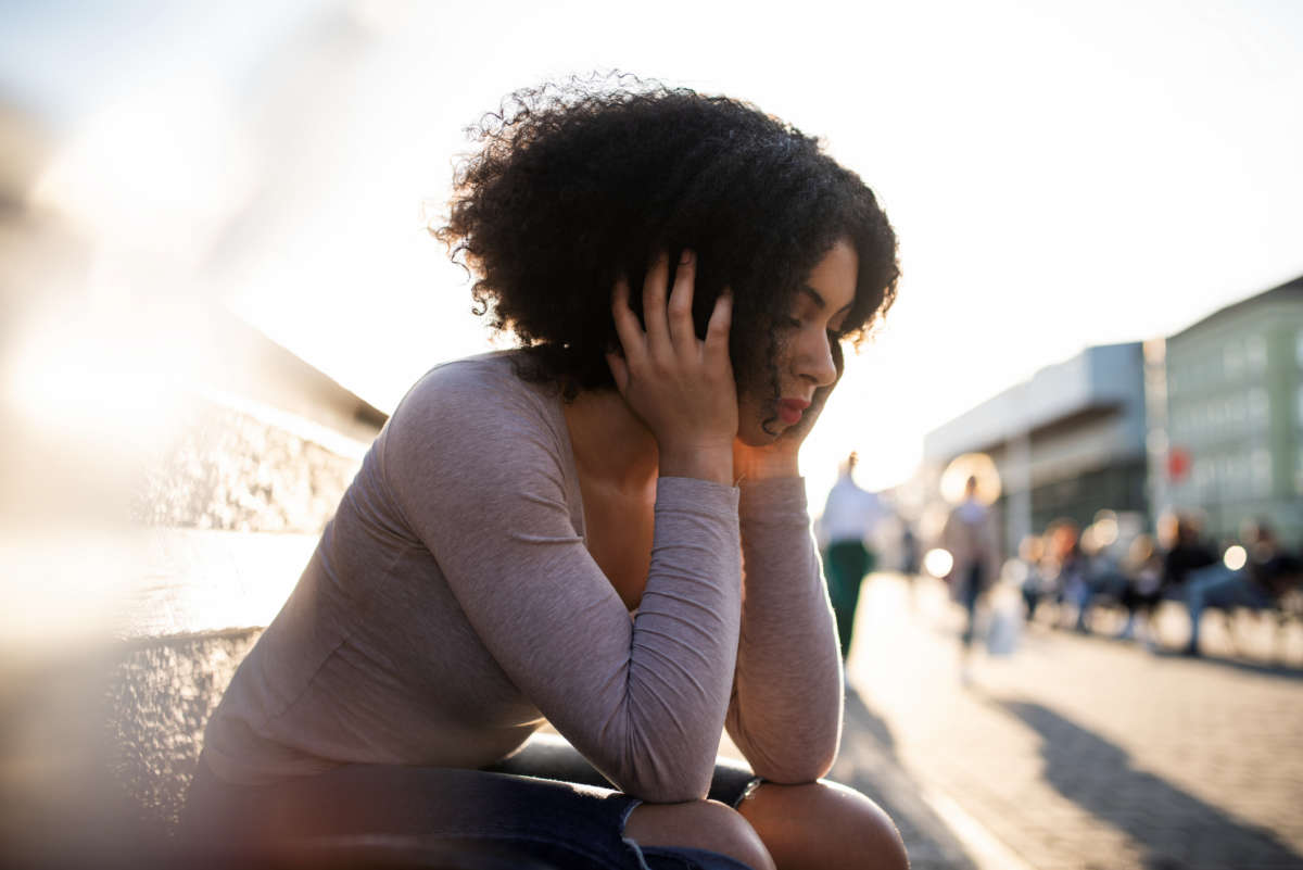 A woman sits on a bench outside holding her head in her hands